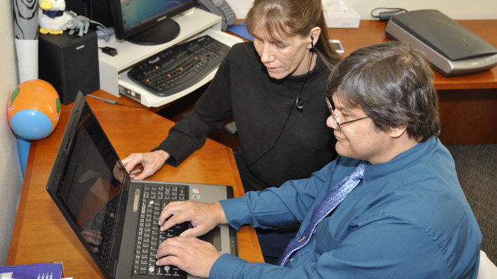 an image of an instructor teaching a student how to use a computer with a screen reader