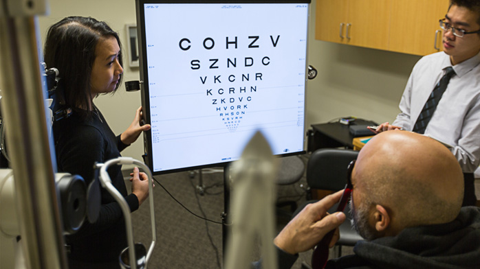 An image of a low vision patient reading letters from an eye chart in the Low Vision Clinic