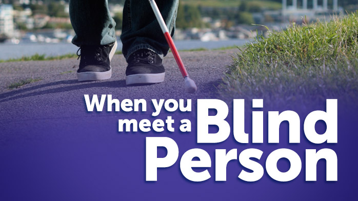 an image of a blind persons feet as they use a white cane to walk along a path with a purple overlay and the words 'When you meet a blind person'