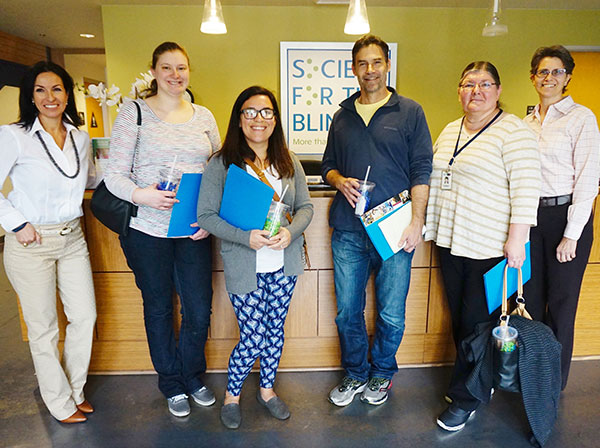 a group of tour guides standing by the front desk at Society For The Blind