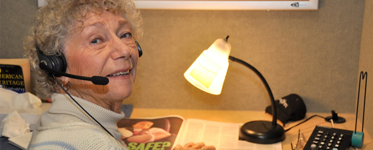 an image of an older woman wearing a headset as she reads for Access News