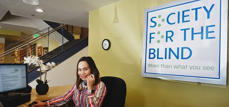 an image of the front desk receptionist sitting behind the reception counter in the lobby of the Society for the Blind building