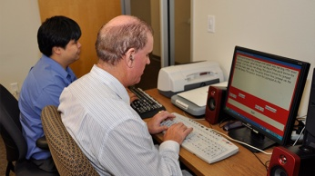 man working at computer in assistive tech class