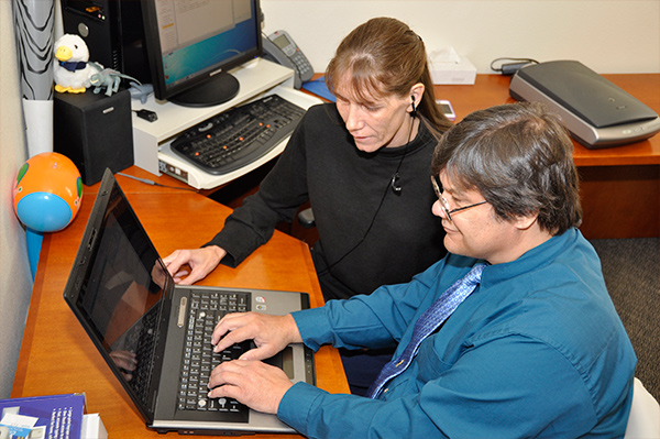 an image of two people at a computer using assistive technology