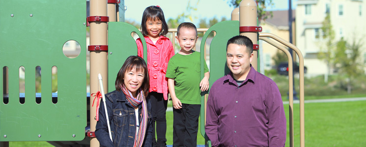 An image of an Asian family standing together in the park for a photograph. The mother is holding a white cane.