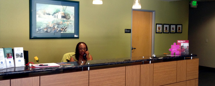 an image of the front desk receptionist, Debra Pendleton, sitting behind the reception counter in the lobby of the Society for the Blind building