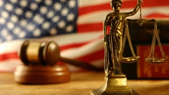 Image of lady justice and scales with judges gavel and american flag