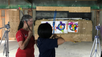 Janice Walth assists an NFC participant during archery at Society for the Blind