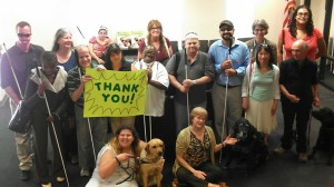 Society for the Blind staff and clients grouped in the lobby, holding a bright neon Thank You sign