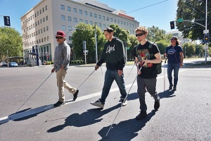 An image of Society staff member and students crossing an intersection using their white canes during an O&M lesson.