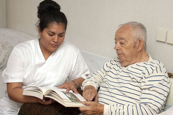 an image showing a woman reading to an elderly man