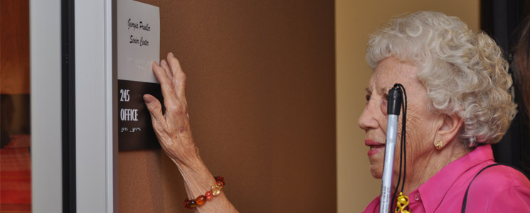 an image of an elderly blind woman feeling the braille on a room sign and holding her white cane