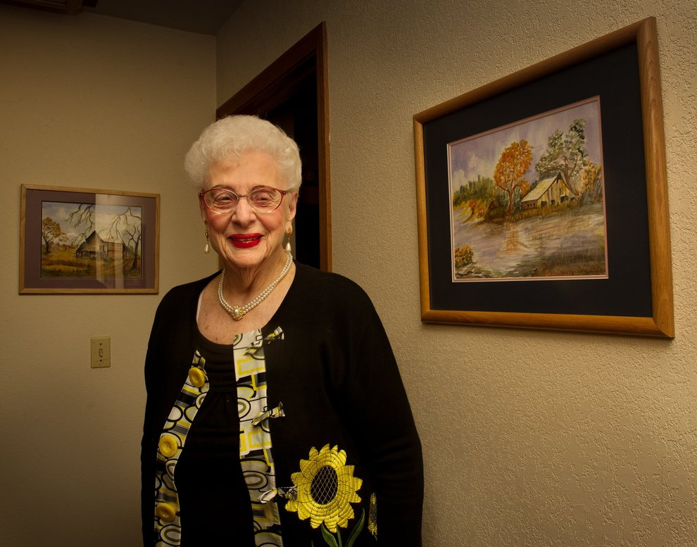 an image of Virgina Bane wearing a black cardigan with a large yellow flower on it smiling for the camera