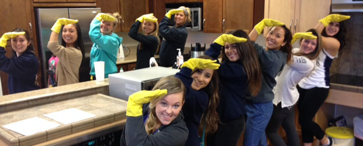 an image of a group of volunteers with yellow dishwashing gloves on standing around a kitchen