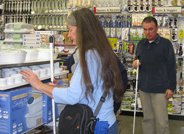 an image of a man and woman couple shopping in a Bed Bath and Beyond with their white canes