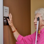 Senior lady finding her way around room Society for the Blind