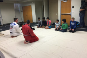 Youth are lined up on mats as they participate in the Judo workshop.
