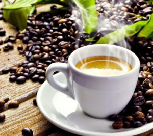 A cup of steaming coffee surrounded by coffee beans