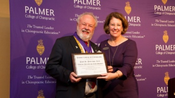 Dr. Paul Peterson receiving his award from Palmer College