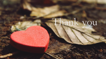 A red heart lays in fall leaves; the words Thank You are printed on the image.