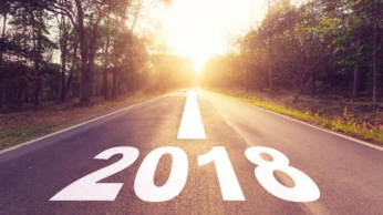 Image a road leading to a sunny horizon; the year 2018 is painted on the road.