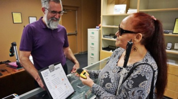 Shirley Garrett receives help from Cory Hanosh at the expanded onsite retail store at Society for the Blind in Sacramento.