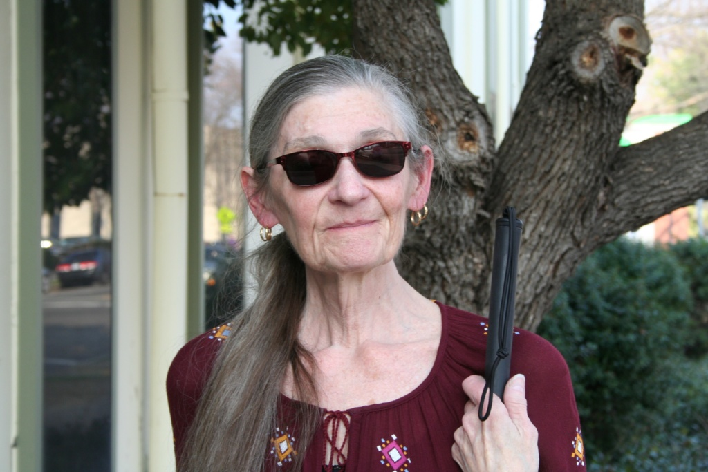 Karon Altman stands with her cane in front of Society for the Blind's building.