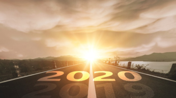 Road leads into sunrise ahead; the year 2019 faded and the year 2020 brightens