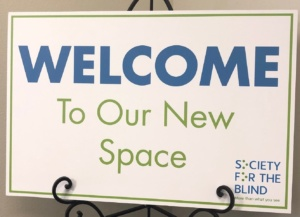 Sign at event. Text reads: Welcome to Our New Space Sign