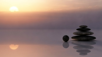 Rocks stacked on a beach with the sun setting in the distance.