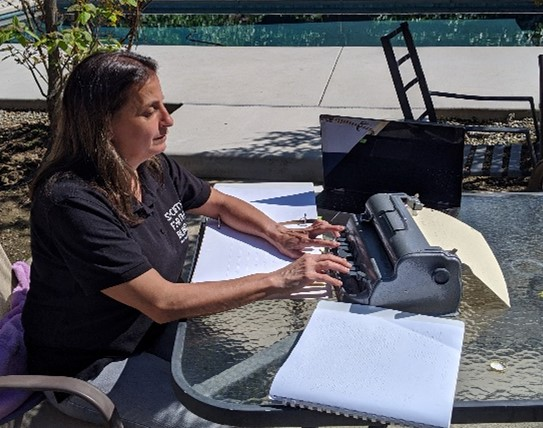 Braille instructor, Jill Guilbeau, creates Braille lessons at a table in her backyard.
