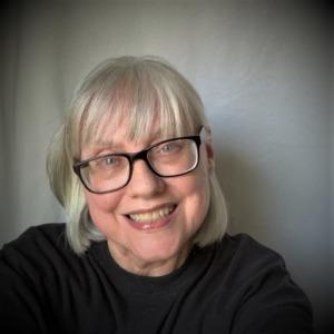 Portrait of Dawn Greene wearing a black top and black glasses.