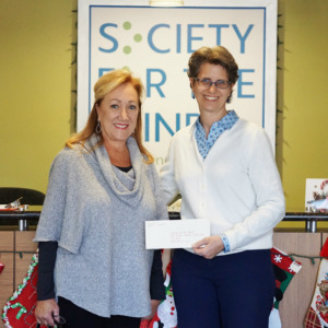Shari Roeseler receiving first grant check from Margaret Whitmire of the M&M Whitmire Family Foundation in December 2017