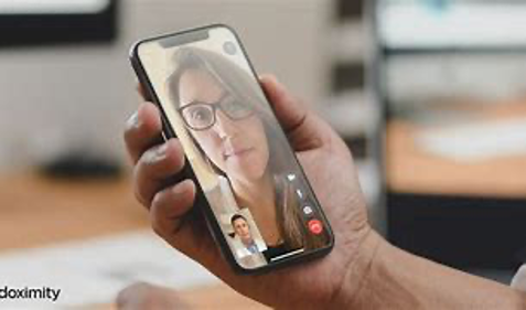 A woman with brown hair having a telemedicine appointment with her doctor via her iPhone