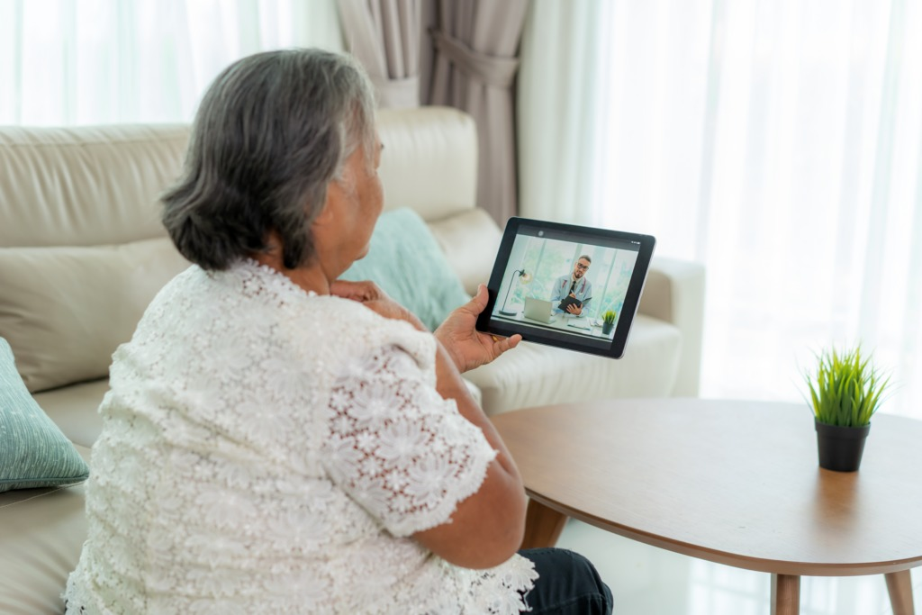Back view of elderly woman making video call with her doctor with her feeling sore throat on digital tablet online healthcare digital technology service consultation while staying at home.