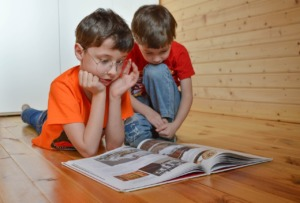 Two school age brothers wearing bright orange read a book that's spread out on the floor.