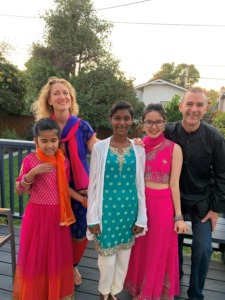 Lisa, Ana Reshma, and family pose for a family photo on their back porch. Lisa and children wear bright, colorful beautiful clothing.