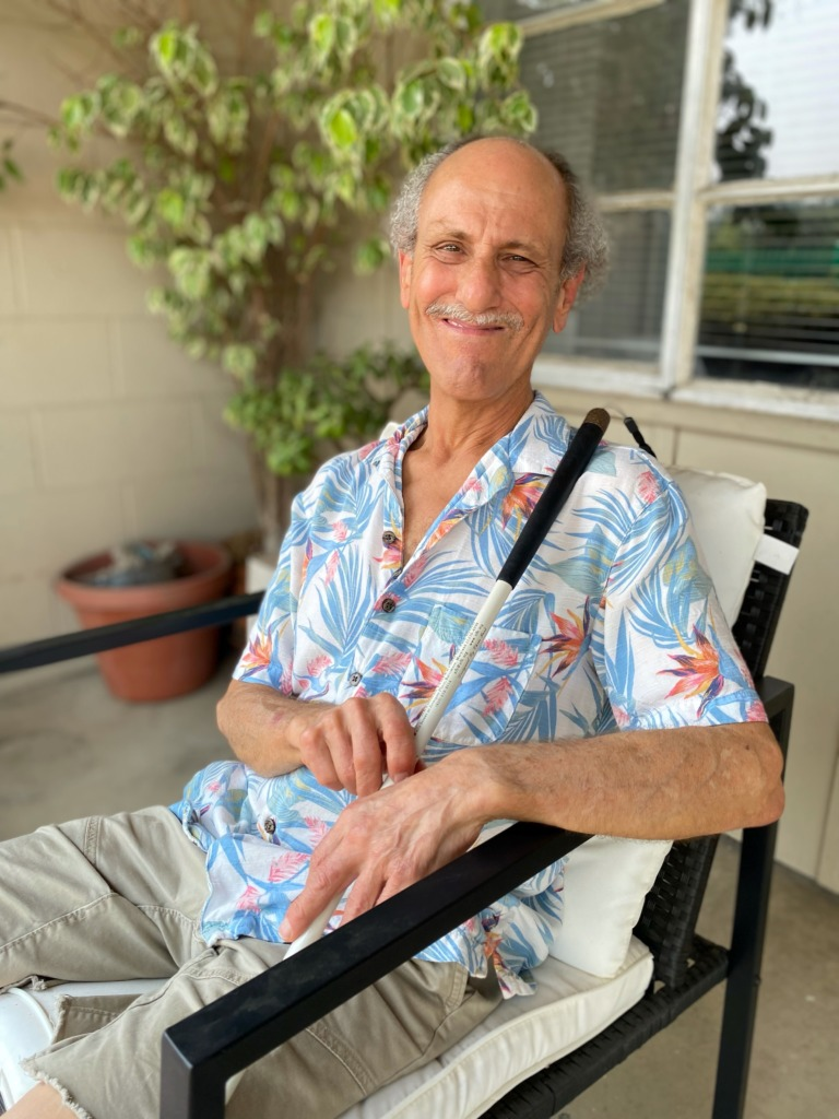 David Moreno wears a blue Hawaiian print shirt and khaki shorts; he's sitting on his front porch in a black chair.