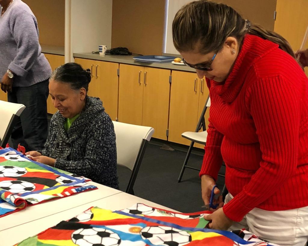 SIP mentor, Mireya Cortes, cuts material during a SIP sewing activity.