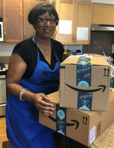 Debra Pendleton stands in the SIP kitchen while holding packages.